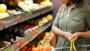 Woman buying fruit and vegetables in grocery store