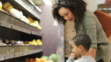 Mother and son buying fruit and vegetables in grocery store