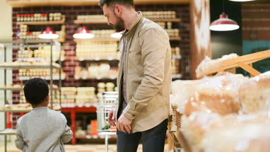Father and son buying bread in grocery store
