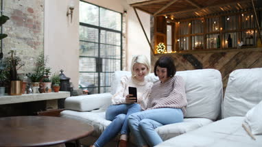 Young adult female friends looking at smartphone at home