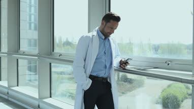 Male medical professional using smartphone in corridor