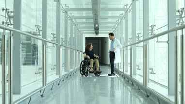 Woman in wheelchair discussing treatment with medical professional