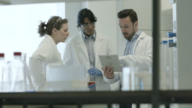 Team of scientists discussing experiment data on digital tablet