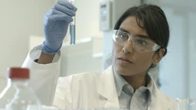 Female scientist analyzing test tube sample