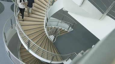 Female business colleagues walking down spiral staircase discussing work