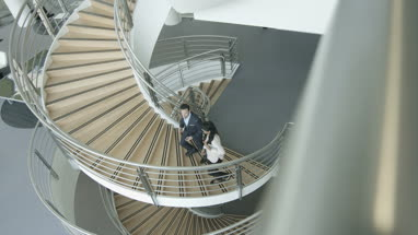 Overhead business colleagues walking up spiral staircase discussing work
