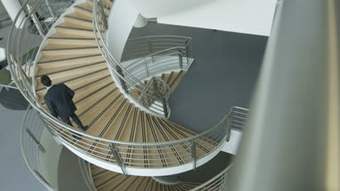 Overhead shot of business executives passing on staircase