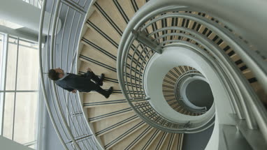 Businessman walking up spiral staircase in office