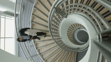 Overhead timelapse of business colleagues walking down spiral staircase discussing work