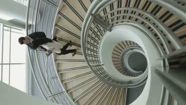 Overhead business colleagues walking down spiral staircase discussing work