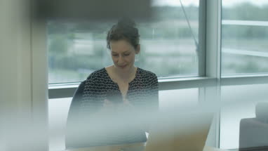 Female executive syncing smartphone to laptop