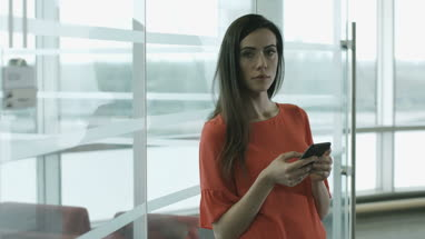Female executive using smartphone waiting for a meeting