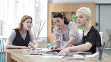 Female designers looking at samples in a meeting