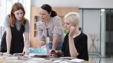 Female designers using smartphone to document project planning