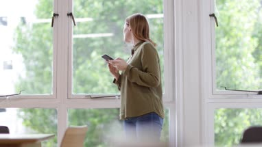 Businesswoman in office looking out of the window and at smartphone
