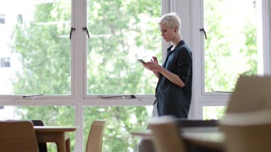 Businesswoman in empty office looking at smartphone
