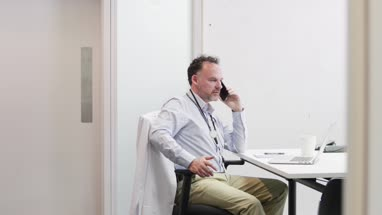 Male Medical Doctor on phone in his office