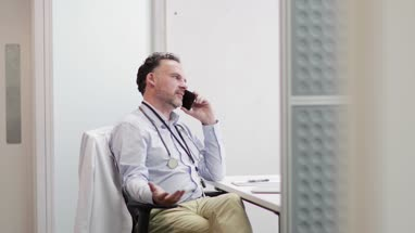 Stressed Medical Doctor on phone in his office
