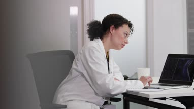 Female Medical Doctor looking at xray results on laptop