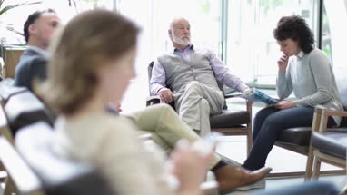 Senior Male waiting in a crowded hospital waiting room