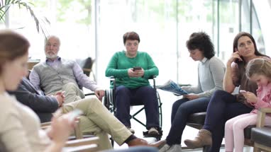 Patients waiting to be called in a crowded hospital waiting room