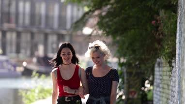 Female friends walking by canal in urban city