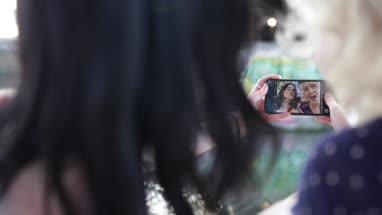 POV female friends taking selfie in urban city