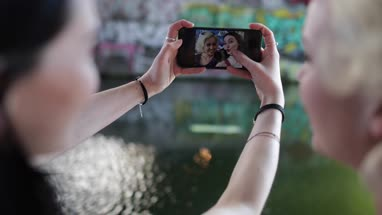 POV female friends reviewing selfies in urban city