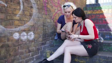 Female friends looking at smartphones in urban city