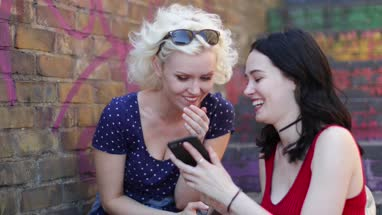 Female friends looking at smartphone and laughing in urban city