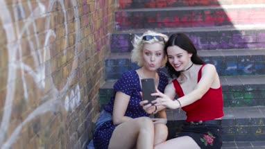Female friends taking selfie in urban city