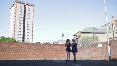 Female friends walking through urban city