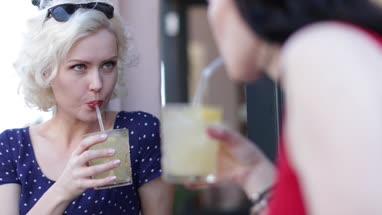 Female friends enjoying a refreshing drink outdoors in summer
