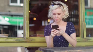 Young adult female using smartphone in bar