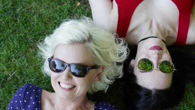 Overhead shot of female friends sunbathing in park