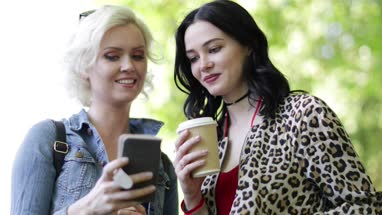 Female friends looking at smartphone and laughing outdoors in summer