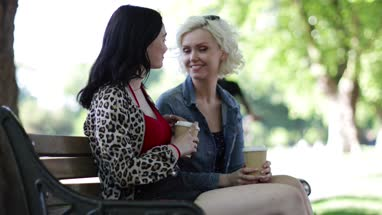 Female friends sitting on bench with takeout coffee in the park