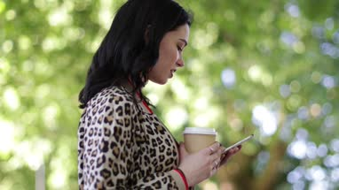 Trendy young adult female using smartphone in park in summertime