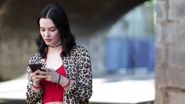 Young adult female using smartphone on street