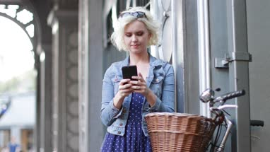 Young adult female with bicycle using smartphone