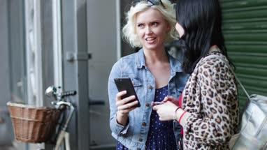 Female friends looking at smartphone in street