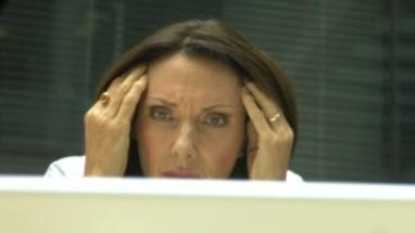 CU FEMALE BEHIND LAPTOP LOOKING STRESSED