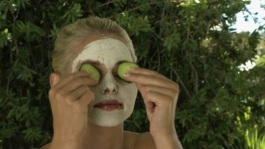 MCU OF A WOMAN WEARING A FACE MASK AND TAKING CUCUMBER OFF HER EYES