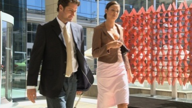 MS PAN OF TWO BUSINESSPEOPLE WALKING OUT OF A HOTEL