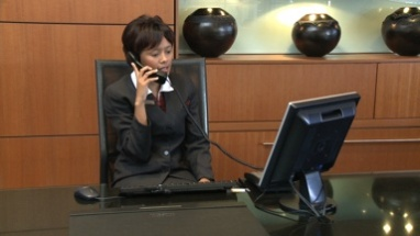 MS PAN OF A RECEPTIONIST ANSWERING A TELEPHONE