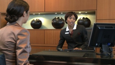 MS OF A BUSINESSWOMAN CHECKING IN AT A RECEPTION DESK