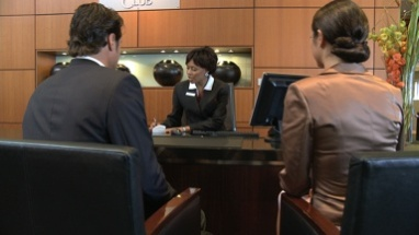 MS OF A BUSINESSMAN AND WOMAN CHECKING IN AT A RECEPTION DESK