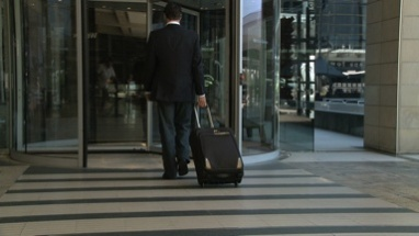 MS PAN OF A BUSINESSMAN WALKING INTO A HOTEL