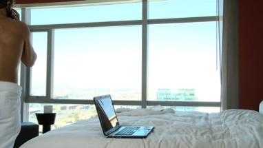 LS PAN OF A BUSINESSMAN IN A TOWEL IN HIS HOTEL ROOM