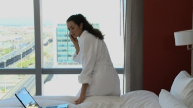 LS PAN OF A BUSINESSWOMAN WORKING IN HER HOTEL ROOM